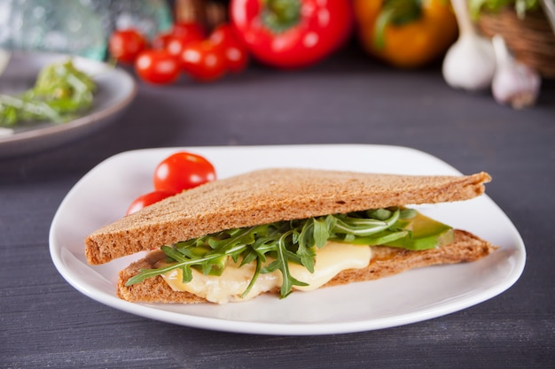 Panino con petto di tacchino, formaggio, lattuga, rucola, pomodori e cipolla su un piatto nero Foto Premium