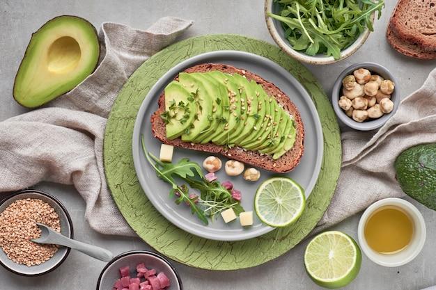 Panino di avocado ed insalata verde con i cubetti di prosciutto su strutturato marrone verde Foto Premium