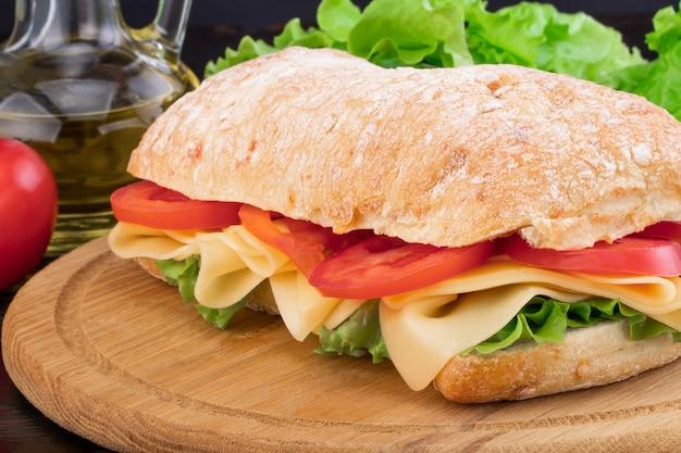 Panino di ciabatta con lattuga, prosciutto e formaggio sul bordo di legno Foto Premium
