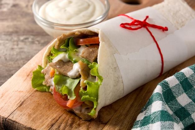 Panino di doner kebab o shawarma sulla tavola di legno. Foto Premium