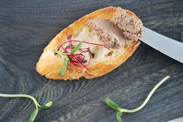 Panino di pane tostato bruciato con patè ed erbe su una tavola di legno scura Foto Premium
