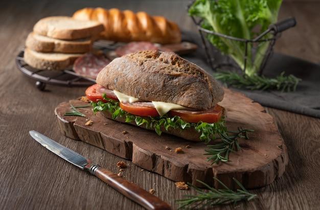 Panino fresco del formaggio del salame con il pomodoro e la lattuga di foglia verde Foto Premium