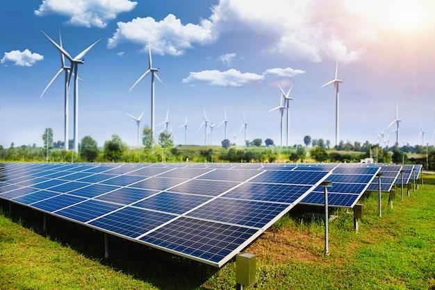 Pannello solare con turbine eoliche contro montagne e cielo Foto Premium