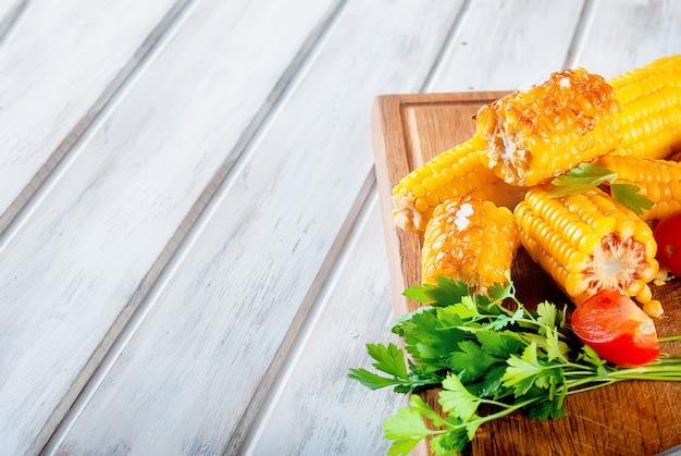 Pannocchie di mais alla griglia con salsa, spezie e pomodori Foto Premium