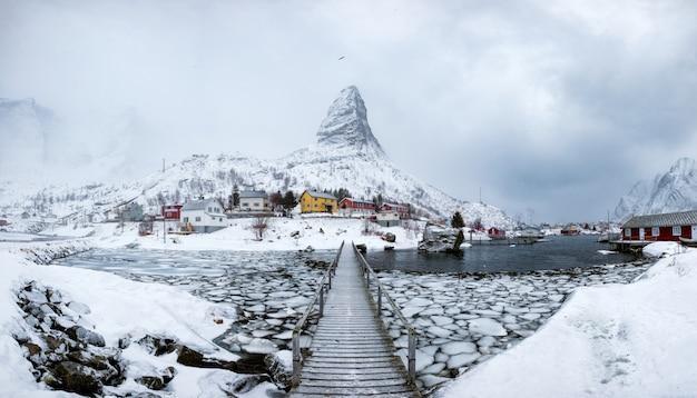 Panorama del villaggio di pescatori nella neve ripida montagna con ponte di legno Foto Premium