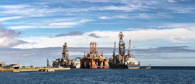 Panorama della piattaforma di perforazione petrolifera nell'oceano con navi di trasporto e bel cielo. Foto Premium