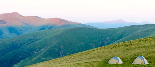 Panorama montano con tenda turistica. alba o tramonto in montagna. concetto di escursionismo. Foto Premium