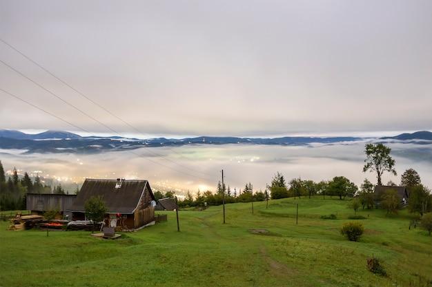 Panorama montano estivo. il piccolo cottage e il granaio di legno della casa sulla valle verde della montagna sul cielo nebbioso luminoso, sulle nuvole e sulla cresta della montagna copiano il fondo dello spazio. Foto Premium