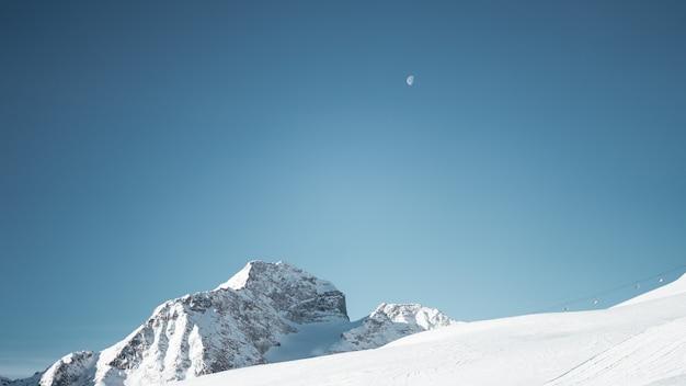 Panoramica di una montagna coperta di neve sotto un cielo blu chiaro con una mezza luna Foto Gratuite