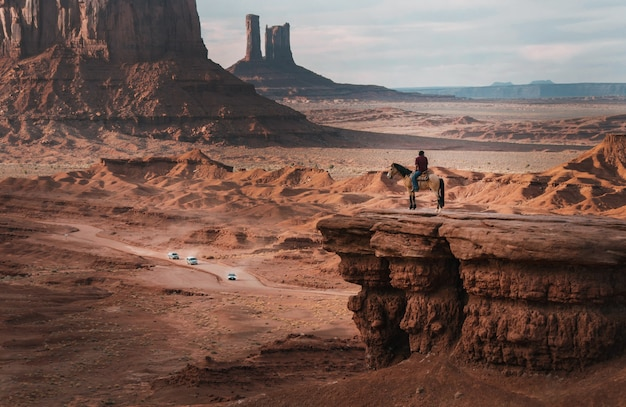 Panoramica di una persona su un cavallo vicino alle scogliere rosse sotto un cielo blu Foto Gratuite