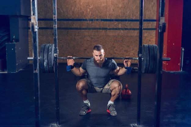 Pantaloni a vita bassa muscolari focalizzati in bilanciere di sollevamento di abbigliamento sportivo in posizione accovacciata. Foto Premium