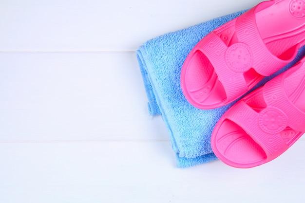 Pantofole, asciugamano su un pavimento di legno bianco Foto Premium