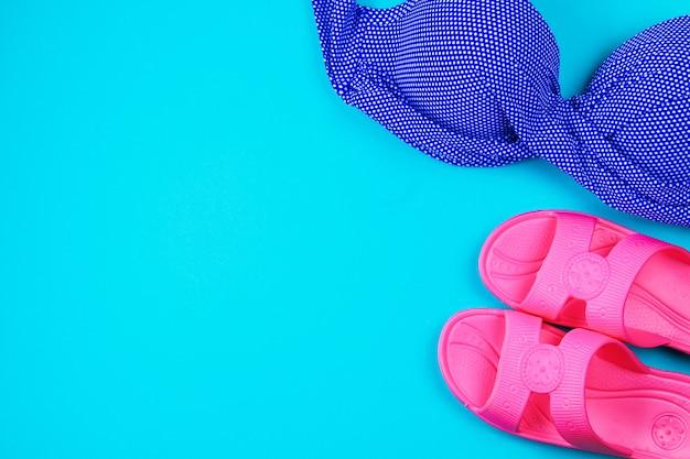 Pantofole, costume da bagno, asciugamano su uno sfondo blu pastello Foto Premium