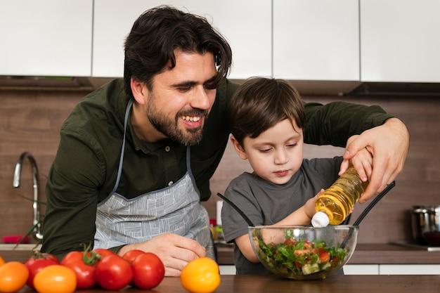 Papà d'aiuto del figlio di vista frontale per produrre insalata Foto Gratuite
