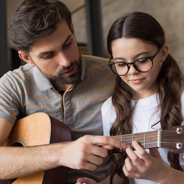 Papà dell'angolo alto che insegna alla ragazza a suonare la chitarra Foto Gratuite