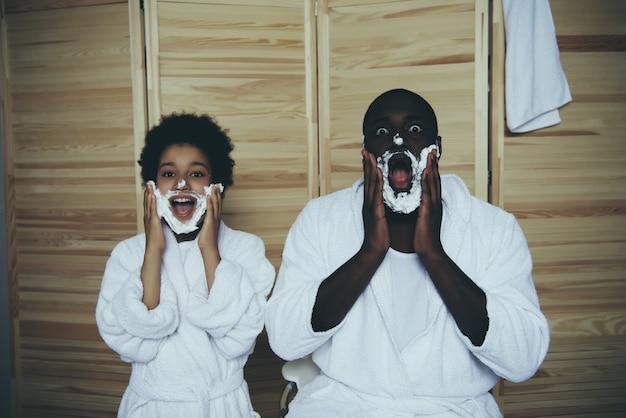 Papà e figlio imbrattati di schiuma da barba e gioiscono. Foto Premium