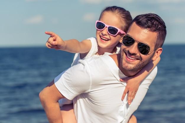 Papà e la sua piccola figlia in occhiali da sole stanno guardando altrove Foto Premium