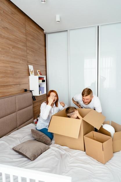 Papà, mamma e figlio piccolo giocano in camera da letto con scatole di carta Foto Gratuite