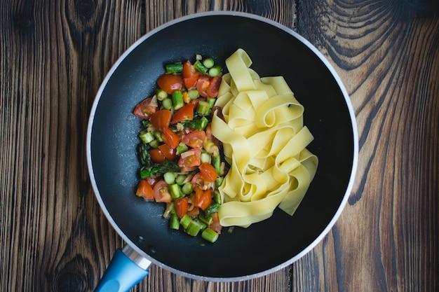 Papardelle con pomodoro e asparagi in padella Foto Gratuite
