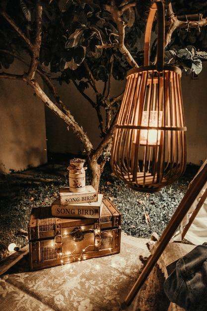 Paralume in legno e una cassa di legno con libri su di esso collocato in un giardino Foto Gratuite