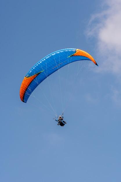 Parapendio nelle alpi svizzere sopra le montagne contro il cielo blu chiaro Foto Premium