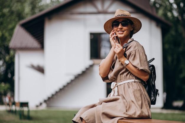 Parco di seduta della giovane donna facendo uso del telefono Foto Gratuite