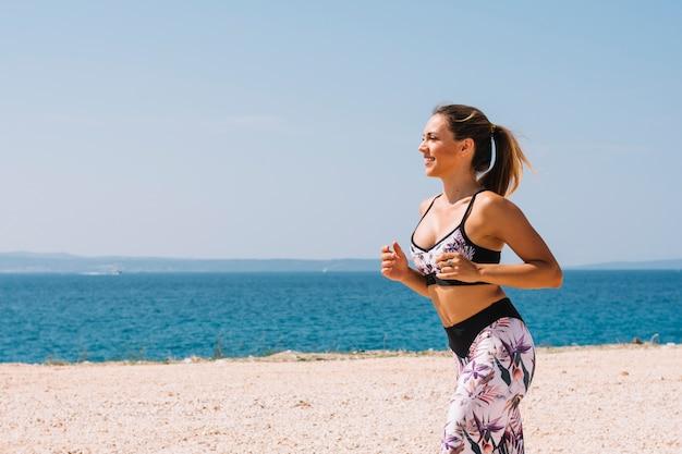 Pareggiatore femminile che corre vicino al mare alla spiaggia Foto Gratuite