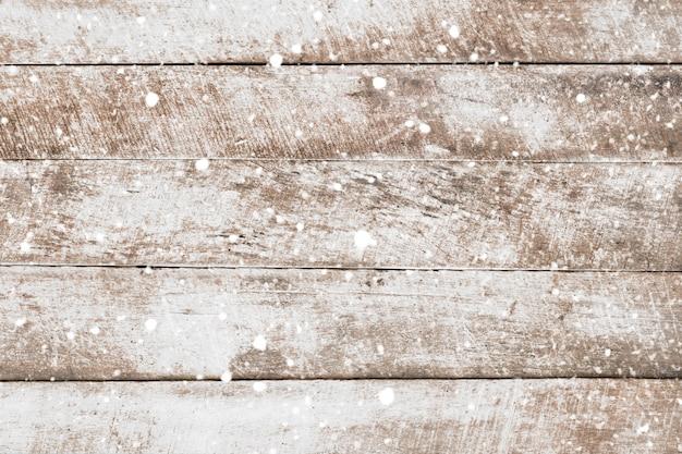 Parete di legno bianca d'annata con neve che cade. fondo rustico di natale, scena invernale. Foto Premium