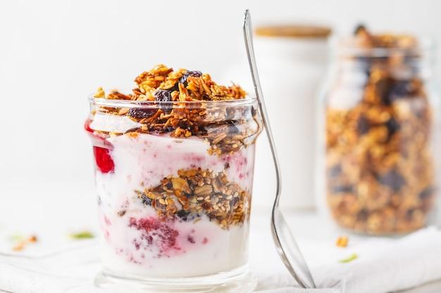 Parfait sano della prima colazione al forno del granola, dell'ostruzione e dello yogurt in vetro. Foto Premium