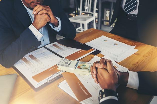 Parlando di affari seri. gente di affari premurosa tenendosi per mano afferrato e guardando al socio commerciale mentre era seduto al suo posto di lavoro. Foto Premium