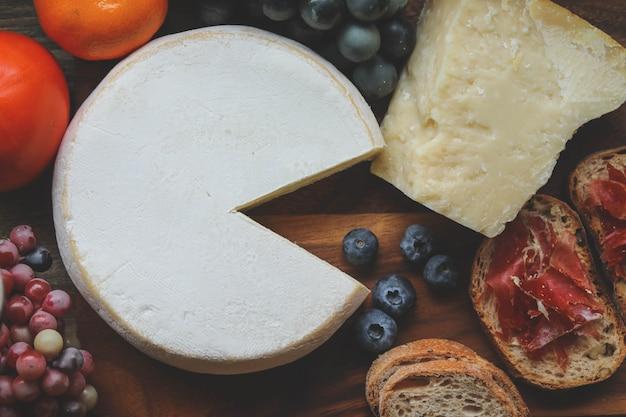 Parmigiano e reblochon sul bordo di legno Foto Premium