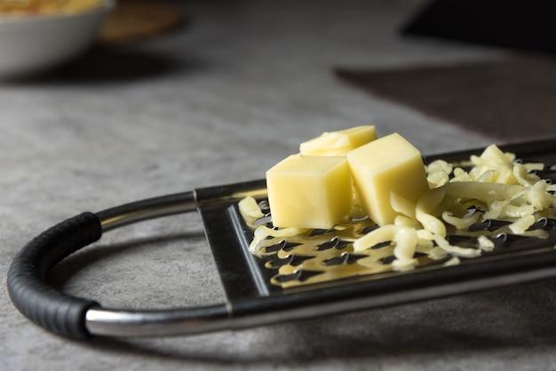 Parmigiano grattugiato, grattugia al formaggio con formaggio cheddar Foto Premium