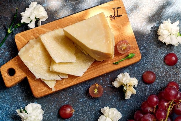 Parmigiano su tagliere in legno con bacche di uva Foto Premium
