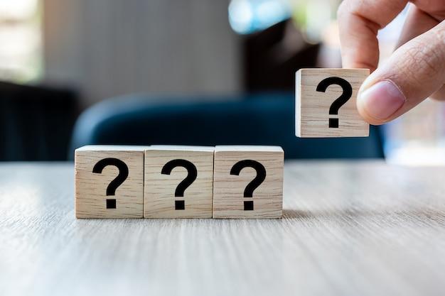 Parola del punto interrogativo (?) della tenuta della mano dell'uomo d'affari con il cubo di legno Foto Premium