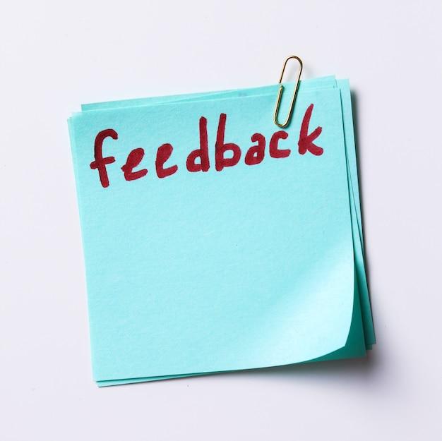 Parola di feedback scritta in una nota cartacea Foto Gratuite