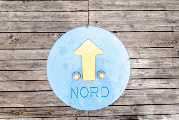 Parola di nord con la freccia di direzione in un cerchio dipinto sul pavimento di legno Foto Premium