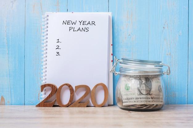 Parola di piani del nuovo anno 2020 su taccuino, vaso di vetro dei soldi e numero di legno. Foto Premium