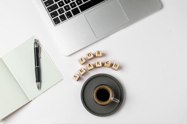 Parola di ricerca di lavoro su timbri in gomma, tazza di caffè, tastiera, penna, blocco note, disoccupazione su grigio Foto Premium