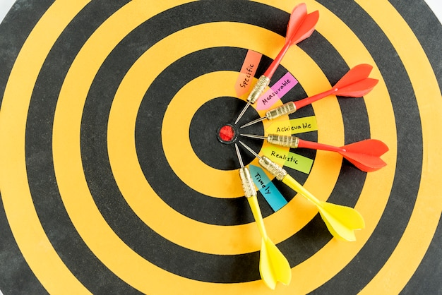 Parole intelligenti con obiettivi dardi sul dartboard Foto Gratuite