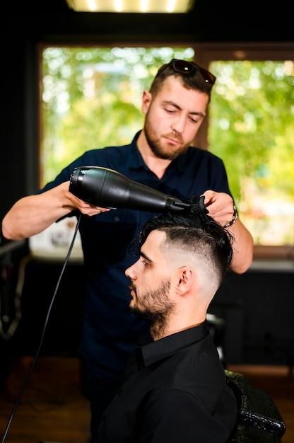 Parrucchiere che asciuga i capelli del suo cliente Foto Gratuite