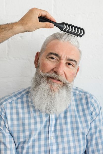 Parrucchiere che corregge acconciatura al cliente anziano Foto Gratuite