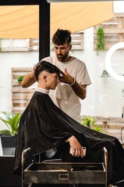 Parrucchiere da uomo. barbiere che fa taglio di capelli nel barbiere. Foto Premium