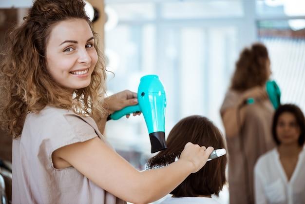 Parrucchiere femminile che sorride, facendo acconciatura alla donna nel salone di bellezza Foto Gratuite