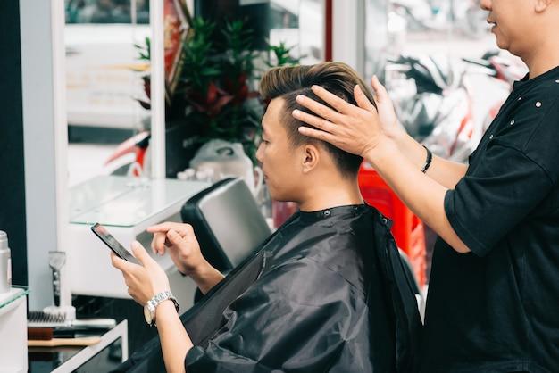 Parrucchiere ritagliato che dà il tocco finale alla pettinatura del cliente maschio Foto Gratuite