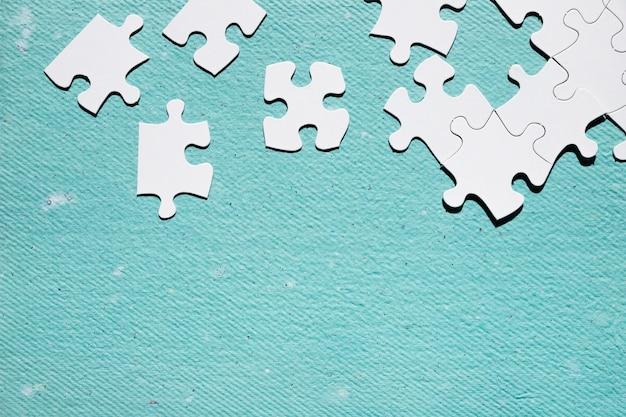 Parte bianca del puzzle sopra superficie strutturata blu Foto Gratuite