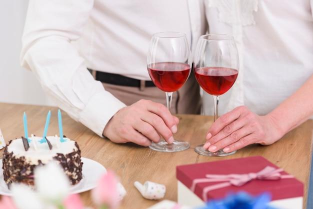 Parte centrale di una coppia in piedi vicino al tavolo con bicchieri da vino; torta di compleanno e confezione regalo Foto Gratuite
