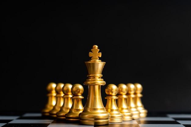 Parte del pezzo degli scacchi re d'oro davanti al pedone sul nero (concetto di leadership, gestione) Foto Premium