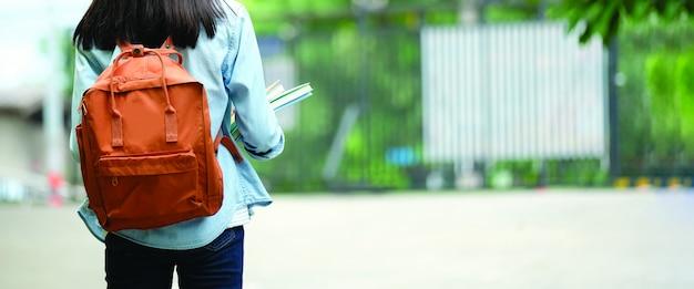 Parte posteriore dello studente universitario con lo zaino mentre andando all'università camminando dalla via, adolescente in città universitaria, concetto di istruzione Foto Premium