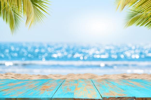 Parte superiore del tavolo in legno con vista sul mare e foglie di palma Foto Premium