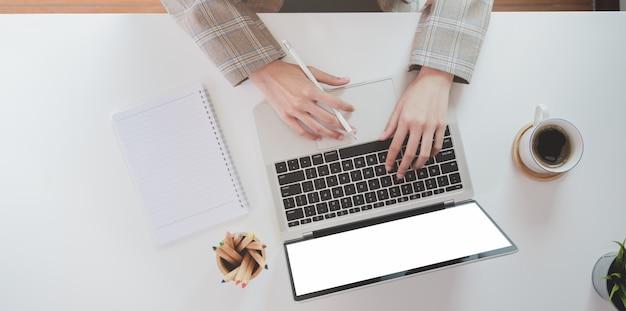 Parte superiore della mano della donna di affari che scrive sul computer portatile Foto Premium
